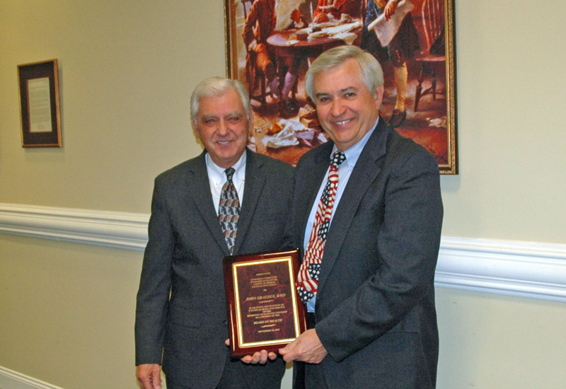 Image of Dr Graeber receiving a plaque from Mayor Ron Francioli